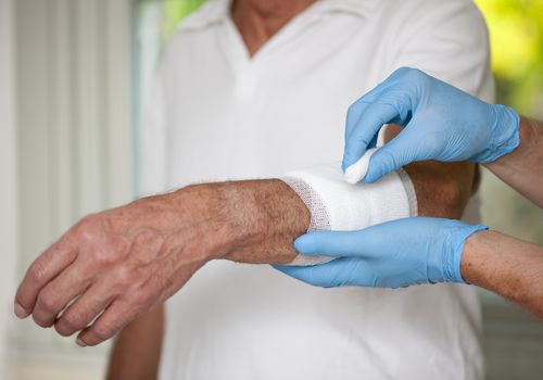 a nurse putting gauze wrap on an elderly patient's arm