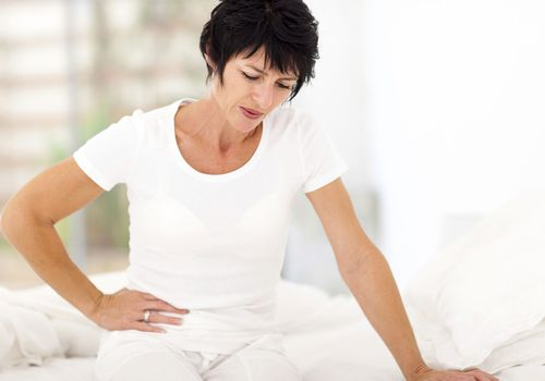 Woman holding her abdomen in pain