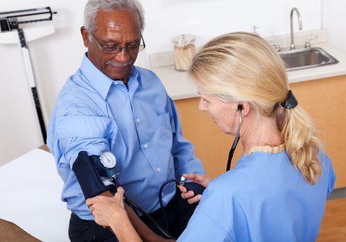 A nurse checking a patient's blood pressure