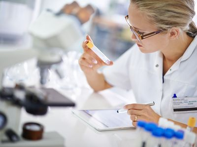 Lab tech looking at sample and recording findings