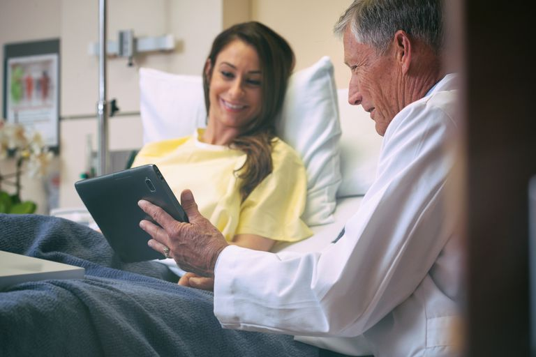 Doctor talking to recovering patient after surgery
