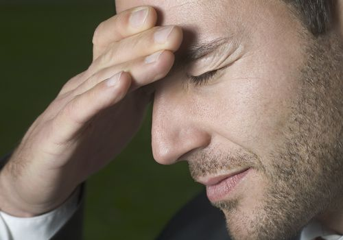 Photo of a man in pain with his hand on his forehead