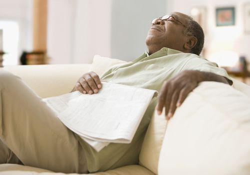 a senior man sleeping on sofa with newspaper