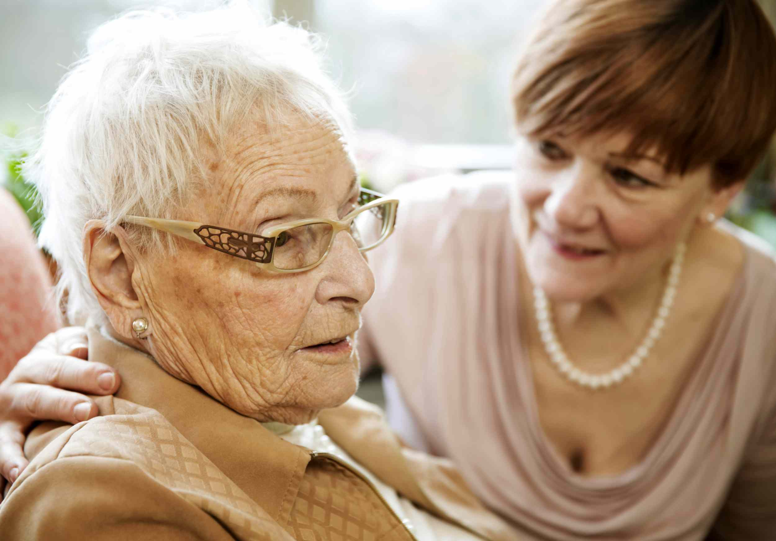 Adult woman looking at an older woman who is staring off into the distance