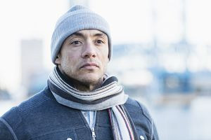 Mid adult hispanic man in hat and scarf stands outside and looks off into distance
