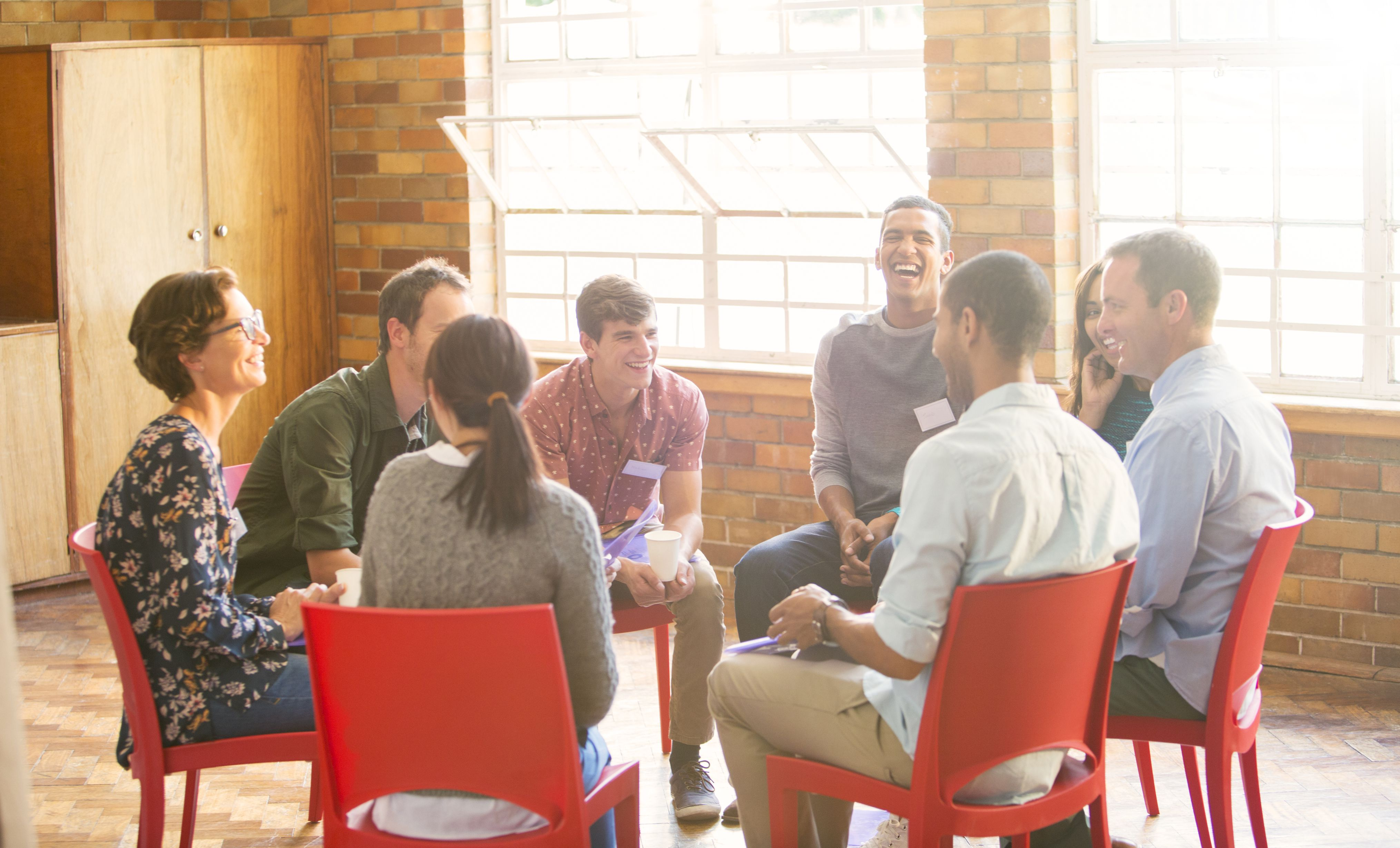 Support group laughing and talking in a circle in bright brick room