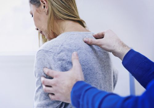 A doctor examining a patient's back