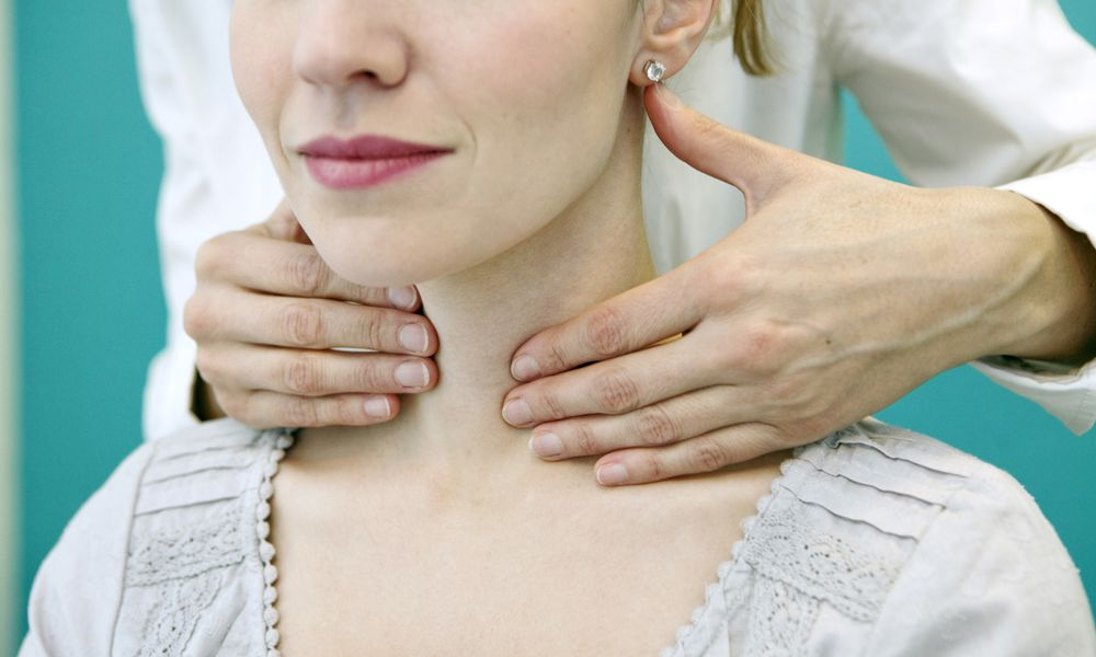 Doctor examining woman's thyroid to evaluate thyroid symptoms