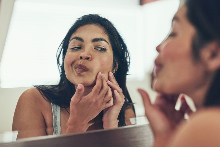 Woman examining skin in mirror
