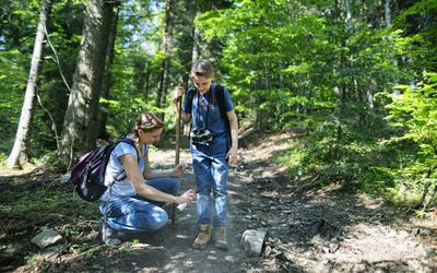 Mom spraying son with bug spray while hiking in woods