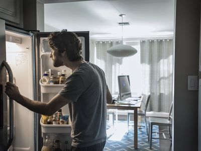 Man standing and looking inside open fridge