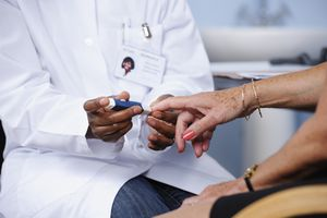 A portrait of medical doctor monitoring a patient's blood sugar/ glucose level.