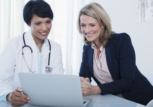 woman and her doctor smiling and looking at a computer screen