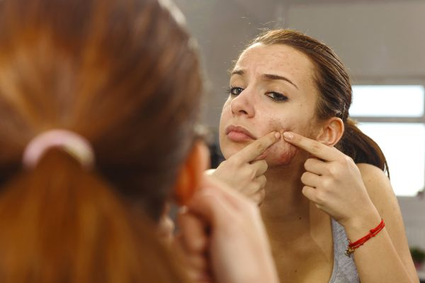 young woman popping a pimple in a mirror