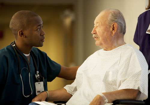 Mature man in a wheelchair with a medical professional