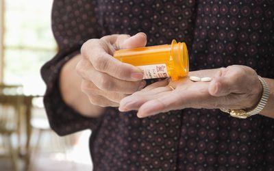 Mixed race woman holding medication pills