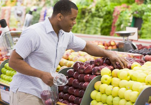 Photo of a man in the produce section of a grocery store selecting apples