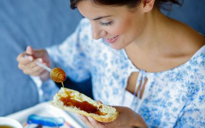 Woman pouring honey on a piece of bread.