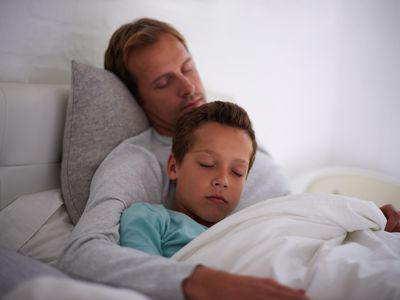 Son lying in bed with sick father