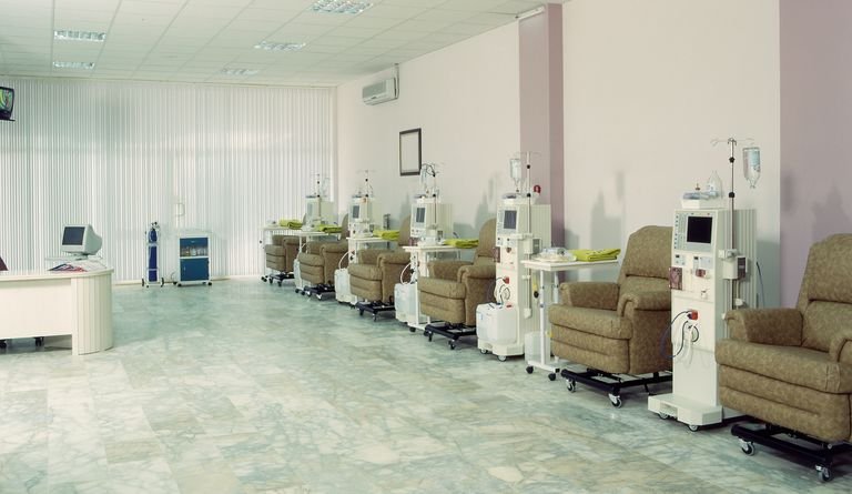 Empty dialysis room with several chairs and machines