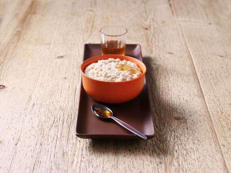 Breakfast bowl of porridge with honey on wood