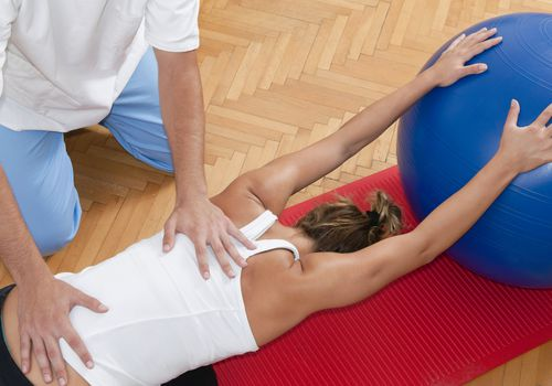 Woman stretching her back with the help of an exercise ball and a physical therapist
