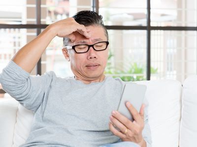 man with glasses getting headache from phone