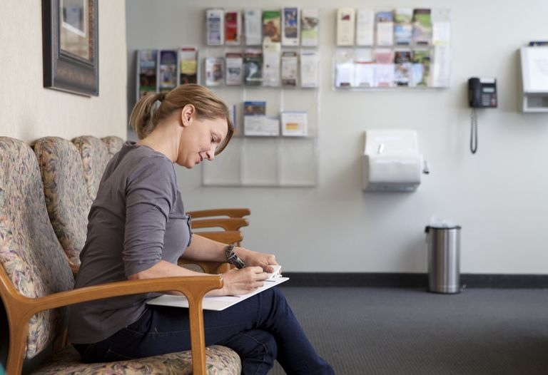 woman filling out paperwork in a doctors office waiting room