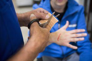 Man cutting bandaid for bleeding friend
