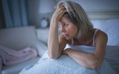 Older woman looking anxious in bed