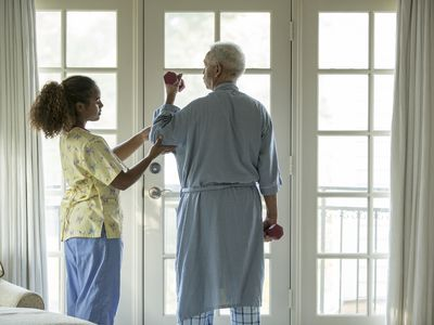 Older man lifting weights during occupational therapy