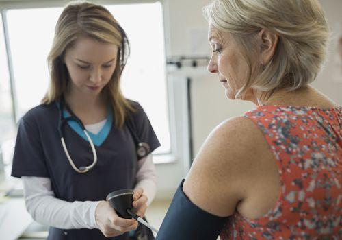 Nurse measuring woman's blood pressure
