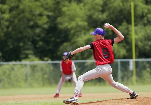 Young pitcher throwing a baseball over his head