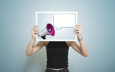 A person's torso holding up an image of a megaphone and speech bubble