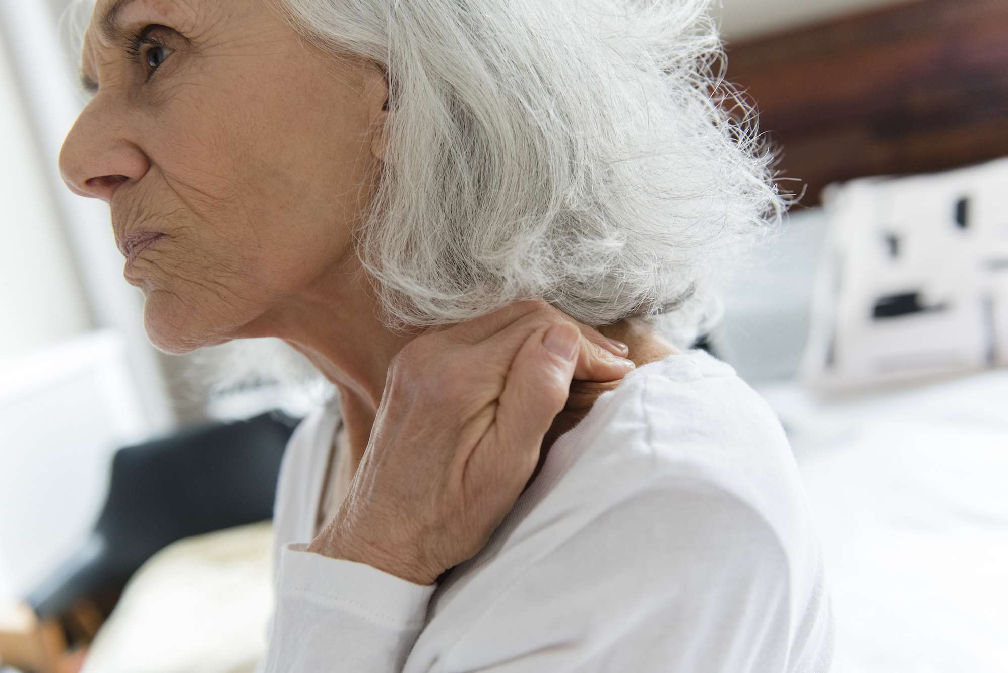 An older woman rubbing her neck