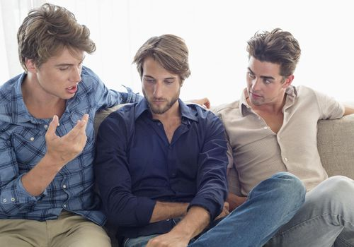Three friends sitting on couch talking together