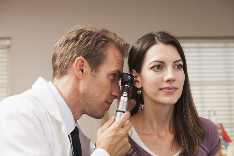 Doctor checking woman's ear