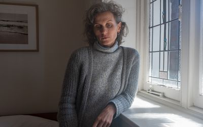 Mature white woman in gray sweater stands by and leans on window and looks down