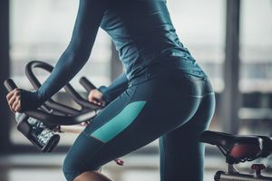 Unrecognizable athletic woman exercising on stationary bike in a gym.