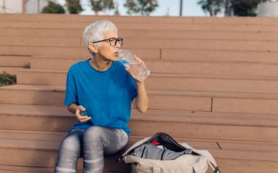 Senior Woman Drinking Water and Preparing to Workout Outdoors