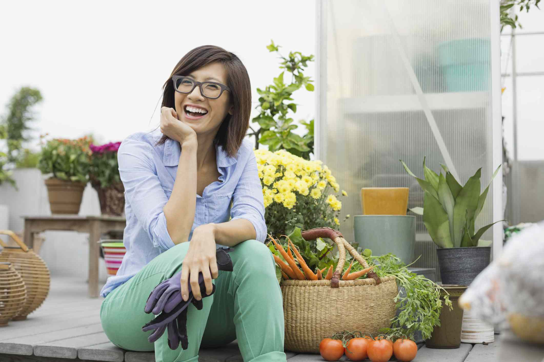Woman sitting on a wooden deck surrounded by plants and vegetables smiling