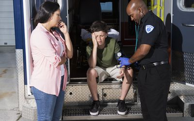 Mother watching paramedic help son - stock photo