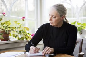 Woman at table writing down thoughts