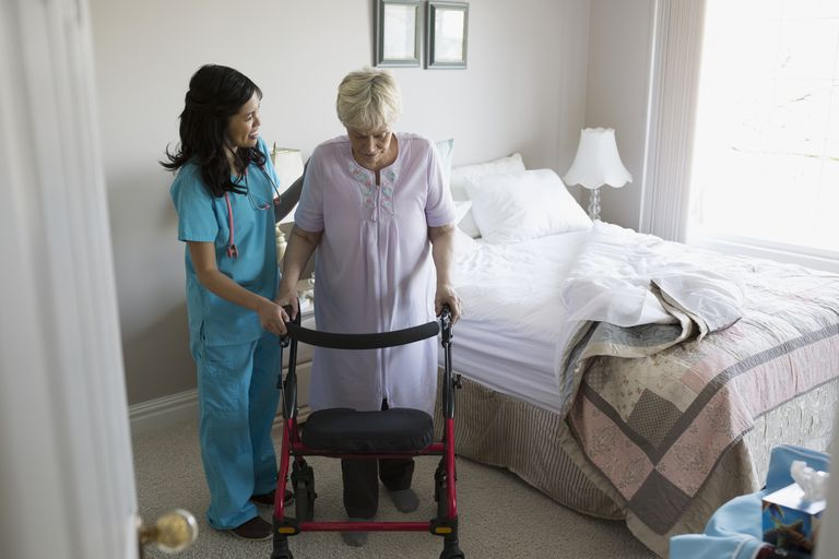 Nurse helping senior woman in nursing home