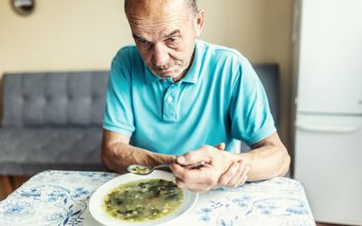 Elderly man with Parkinson's disease holds his arm with a hand, trying to eat soup.
