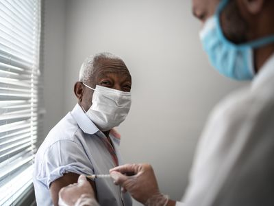 Older Black man wearing a mask and receiving a vaccine from a medical provider