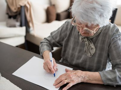 High angle view of a senior woman doing Alzheimer's disease cognitive functions self assessment test at home