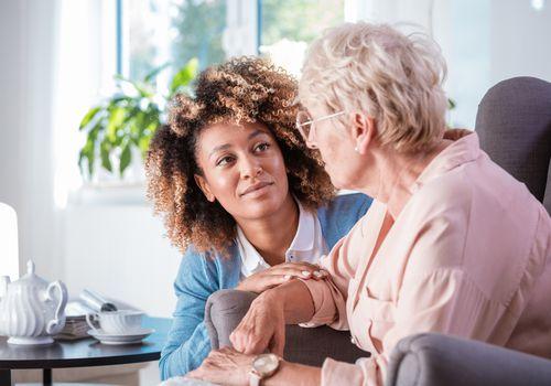 Older woman talking to caretakers