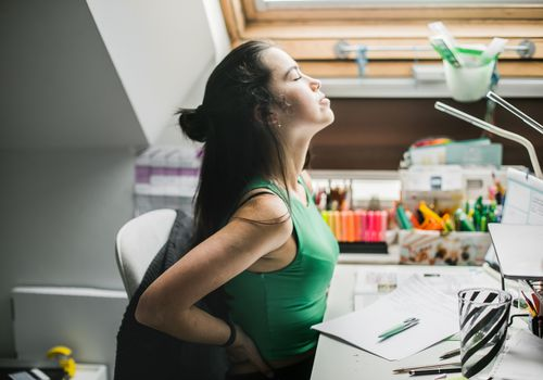 A woman with pale skin and a green shit stretching while sitting down.