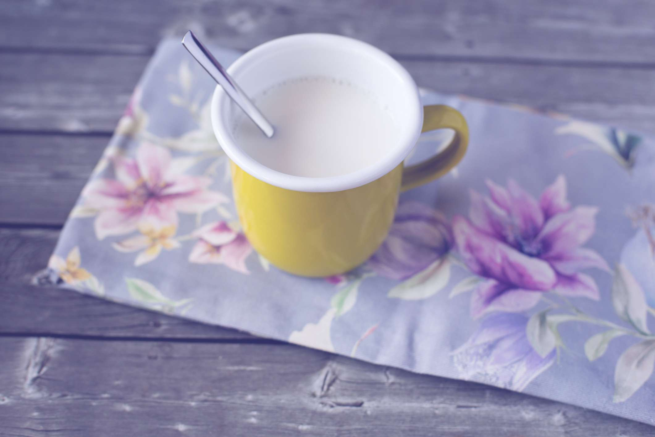 A mug of warm milk with a spoon on a floral napkin.